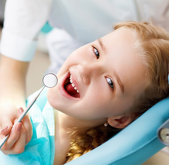 Little girl laughing during dental checkup