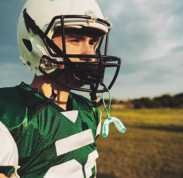 Teen with mouthguard hanging from football helmet