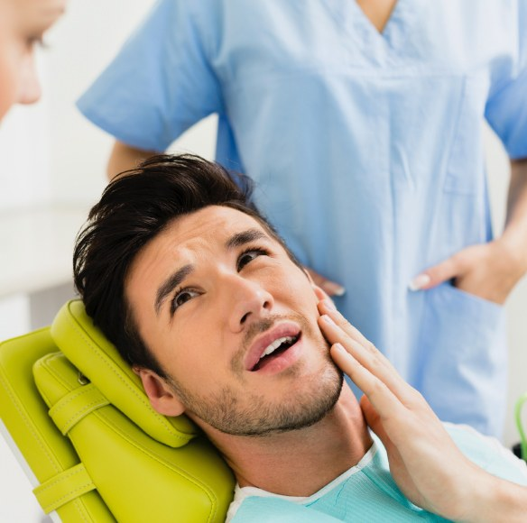 Man in need of emergency dentistry holding cheek in pain