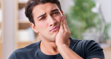 Man with toothache holding cheek in pain