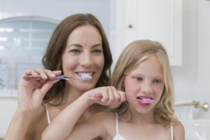 mother and child brushing together